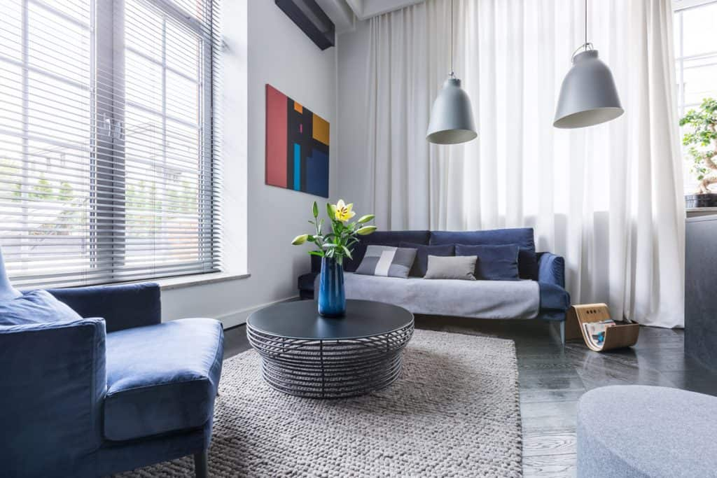 A luxurious living room with blue colored furnitures white walls hanging lamps and gray colored floors