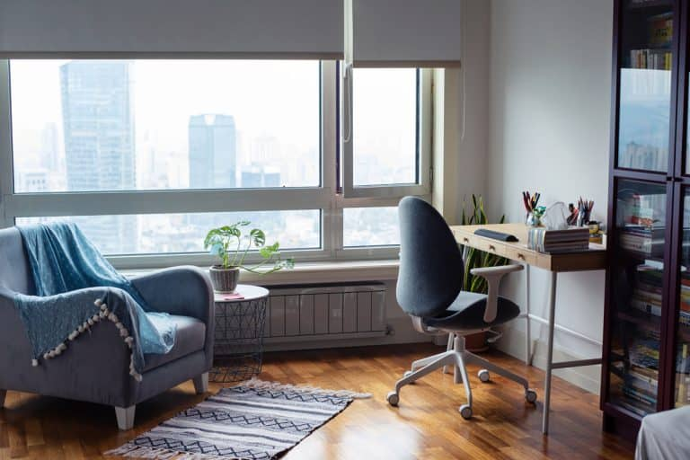 A modern apartment with a computer desk on the side and a small accent chair on the left, What is The Standard Height of a Desk? [And how to find the ideal desk height for you]