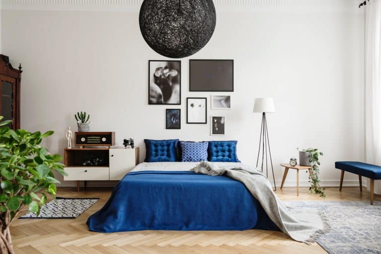 A modern bedroom with blue colored bedskirt, blue pillows, a black and white picture frames hanged on a white colored wall, Does a Bedskirt Need to Reach the Floor?