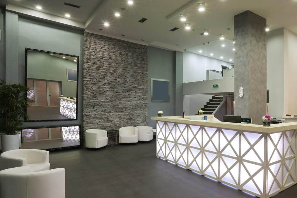 A modern design reception area of a hotel with a noticeable faux decorated wall and a grooming are with a huge mirror