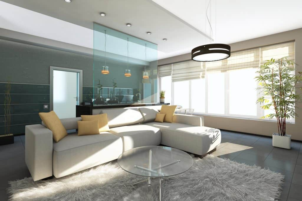 A modern living room with a glass wall in the kitchen beige colored sofa and rug with light yellow colored throw pillows
