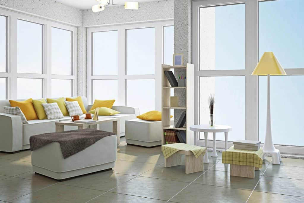 A modern living room with white couches, gray flooring and yellow throw pillows