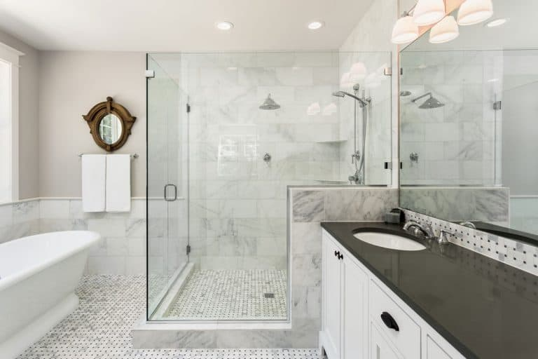 A modern white themed bathroom with a glass wall shower area and a small tiled flooring, Does Bathroom Floor Tile Have To Match Shower Tile?