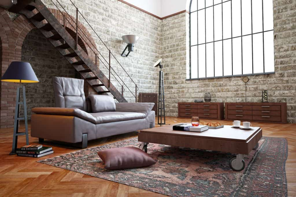 A post industrial themed living room incorporated with stone decorated wall and a Mediterranean themed window
