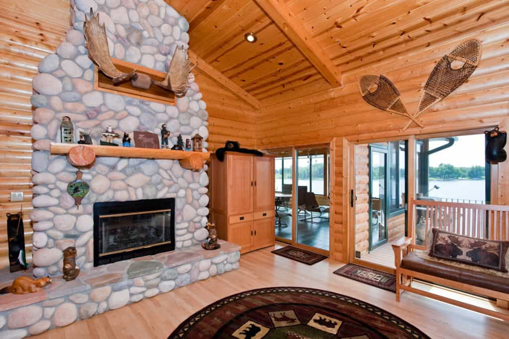 A rustic house with a wooden panel from the ceiling to the flooring and a stone decorated fireplace