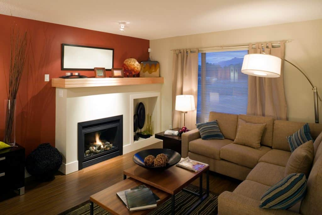 A small living room with brown couches and a fireplace with white colored mantel