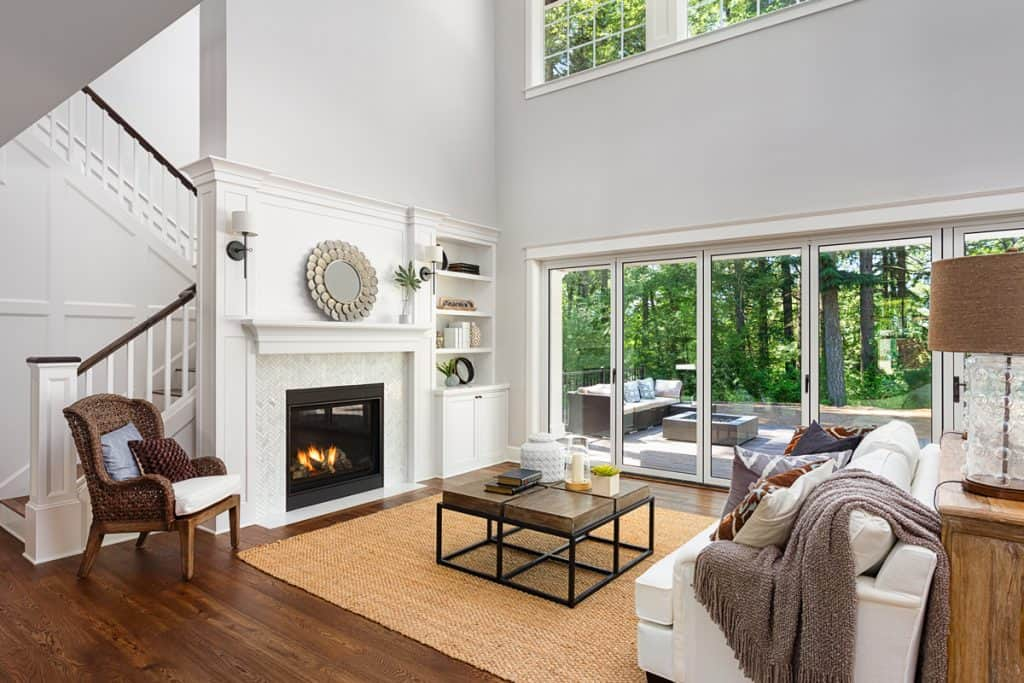 A spacious two storey modern contemporary house with huge windows, white couches, and a fireplace with a white colored mantel