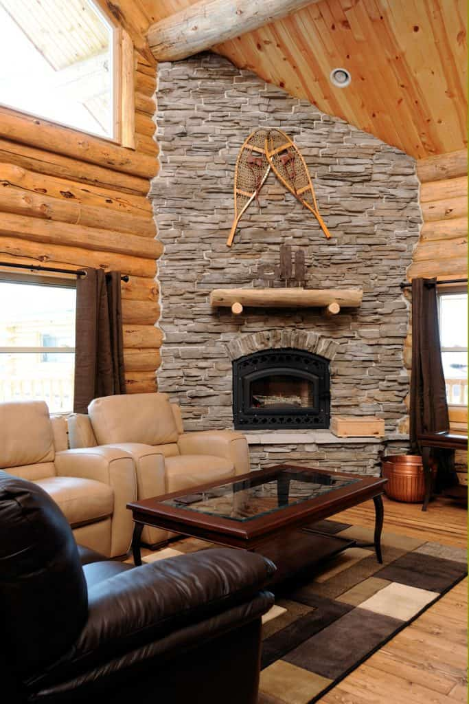 A stone decorated fireplace blended together with wooden paneled wall and rustic themed furnitures