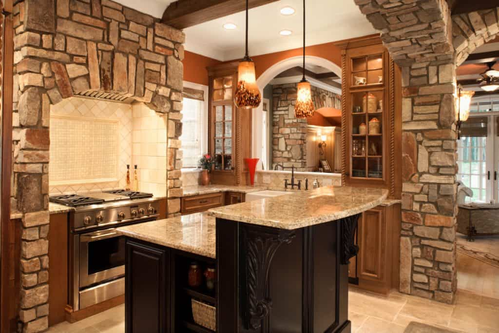 A stone themed house with a wooden panel cover in the oven area and a beam decorated with faux stones