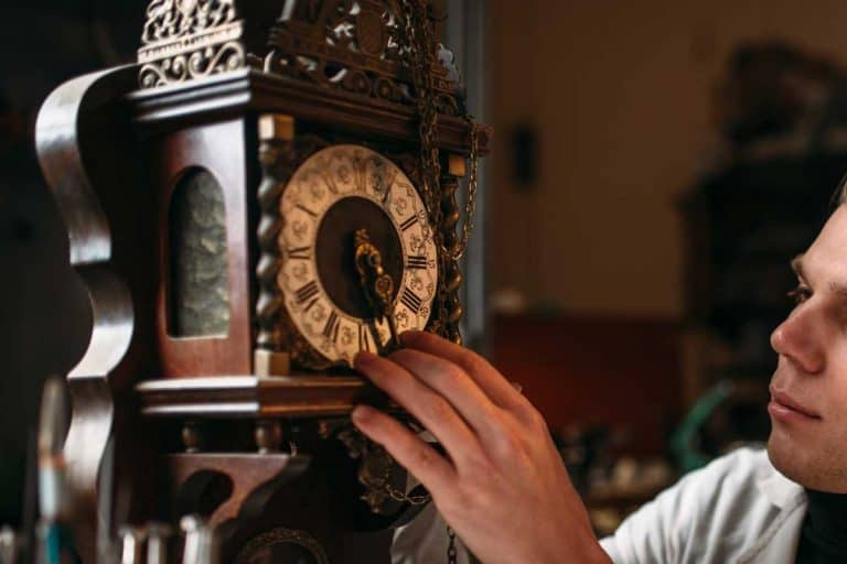 A watchmaker repairs the old grandfather clock, How Much Does It Cost To Service A Grandfather Clock?