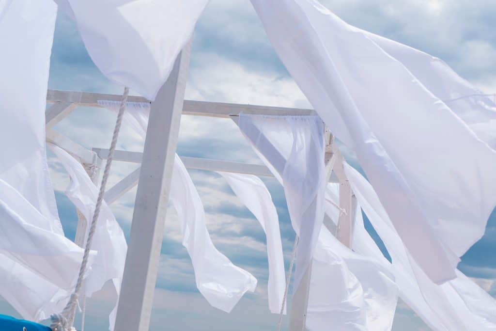 A white colored hanging curtain blowing in the wind