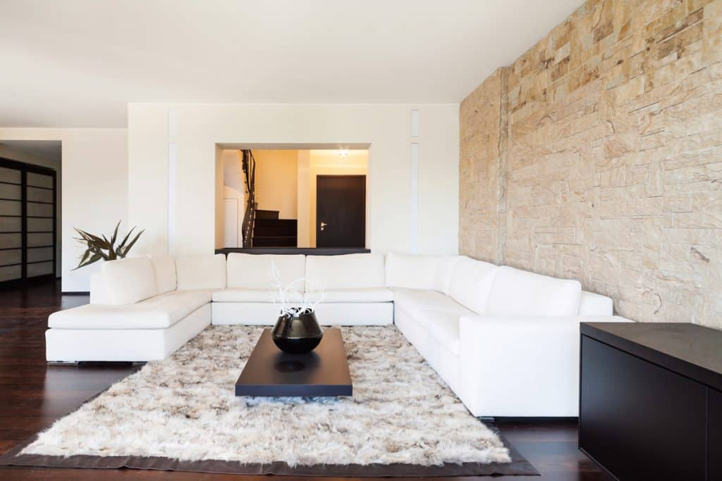 A white colored living room with a white sectional couch and an area rug on the center and a beautiful stone decorated wall