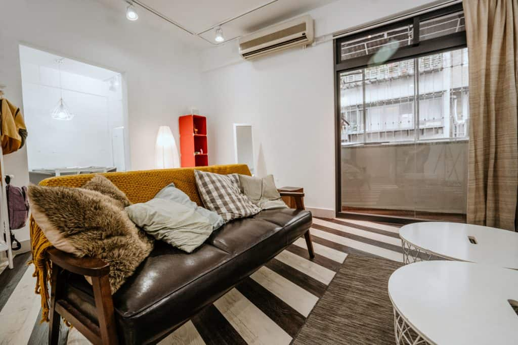 A white walled living room consolidated with a striped flooring and brown furnitures