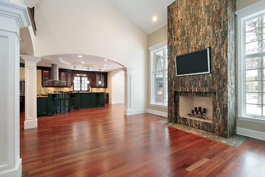 An empty space in a house with a fireplace decorated with stone patterned walls