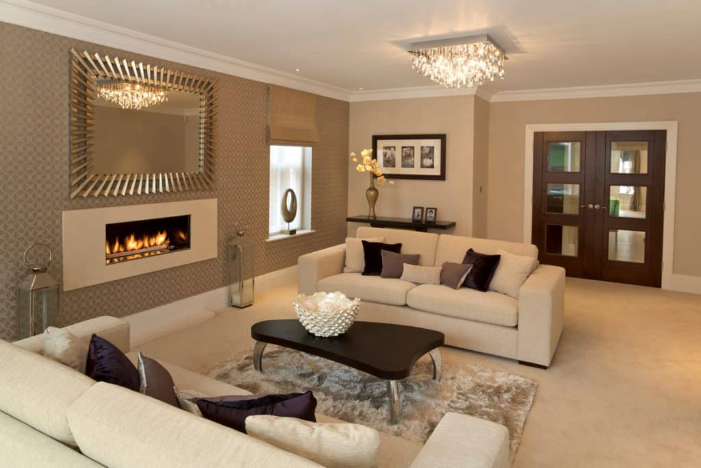 An incorporation of the colored brown beige and black on a living room with a fireplace on the left