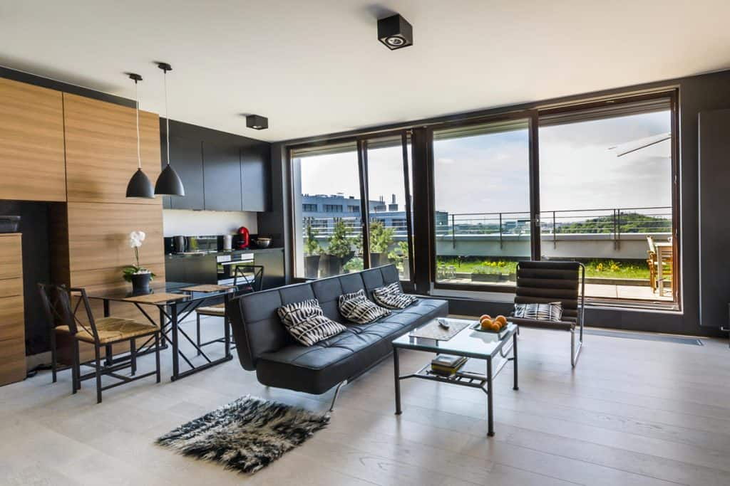 An industrial themed living room with black colored chairs and a huge windows in the background with a scenic view