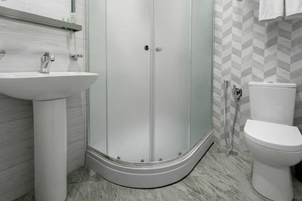 Bathroom with tiles and bright colors of broom shower with frosted shower doors