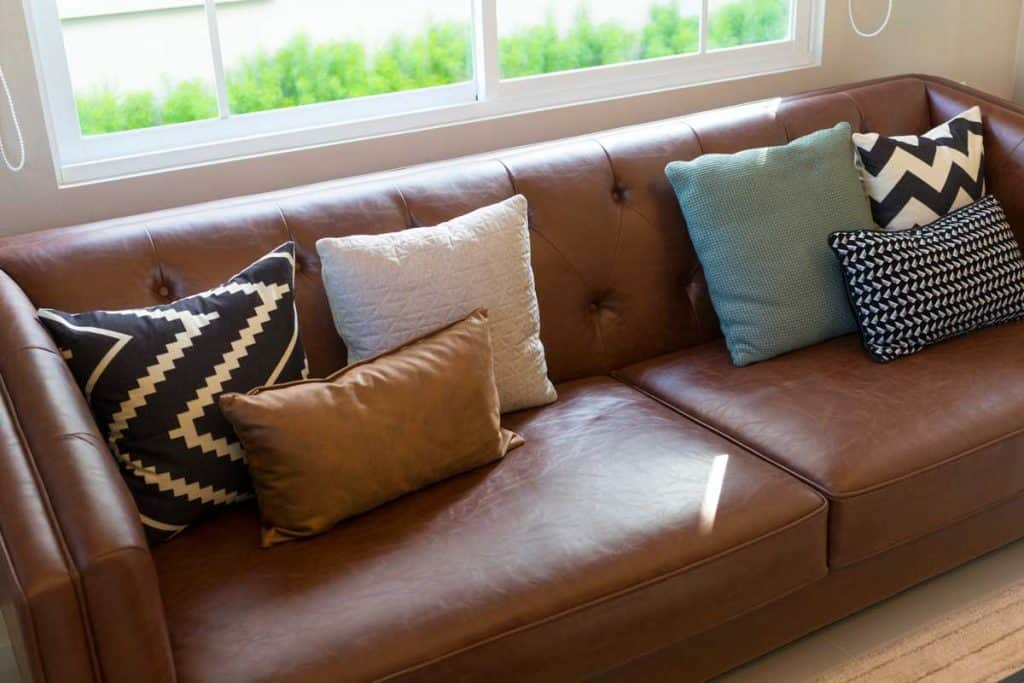 Brown leather sofa with graphic pattern pillow in elegant living room interior by the window. Modern stylish interior