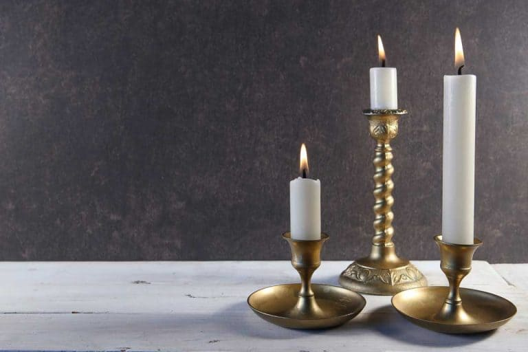 Burning candles in vintage metal candlesticks on white wooden table, What Can You Put In A Candle Holder Besides Candles?