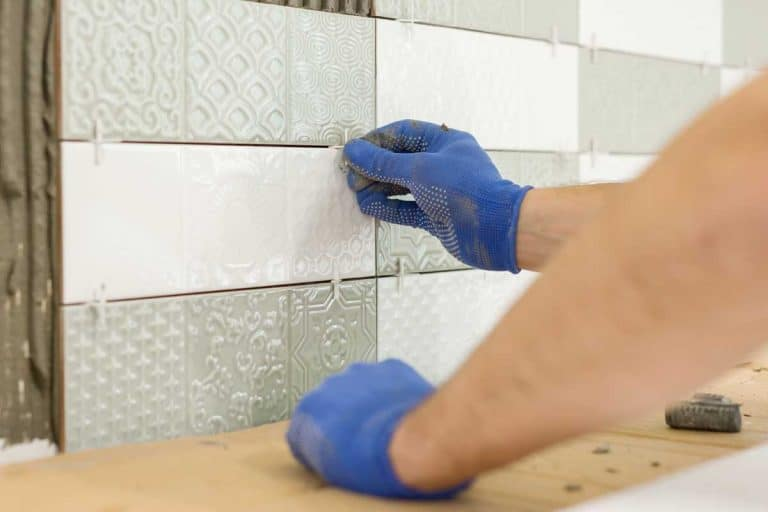 Closeup of tiler hand installing ceramic tiles on the wall, Should Kitchen And Bathroom Tile Match?
