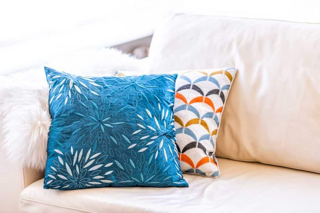 Closeup of two blue and orange pillows on couch or sofa by bright window in modern apartment, house or home with staging of large beige, neutral white colors