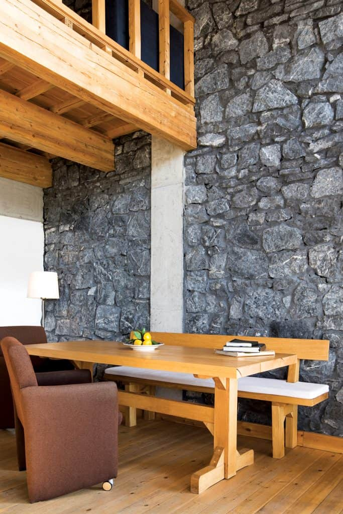 Decorative stone installed on the walls incorporated with a rustic themed living room with wooden tables and brown upholstered char