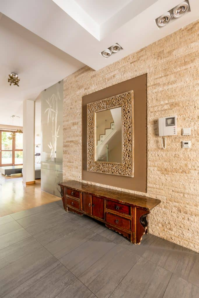 Decorative stone pattern on the wall with a stone patterned mirror frame