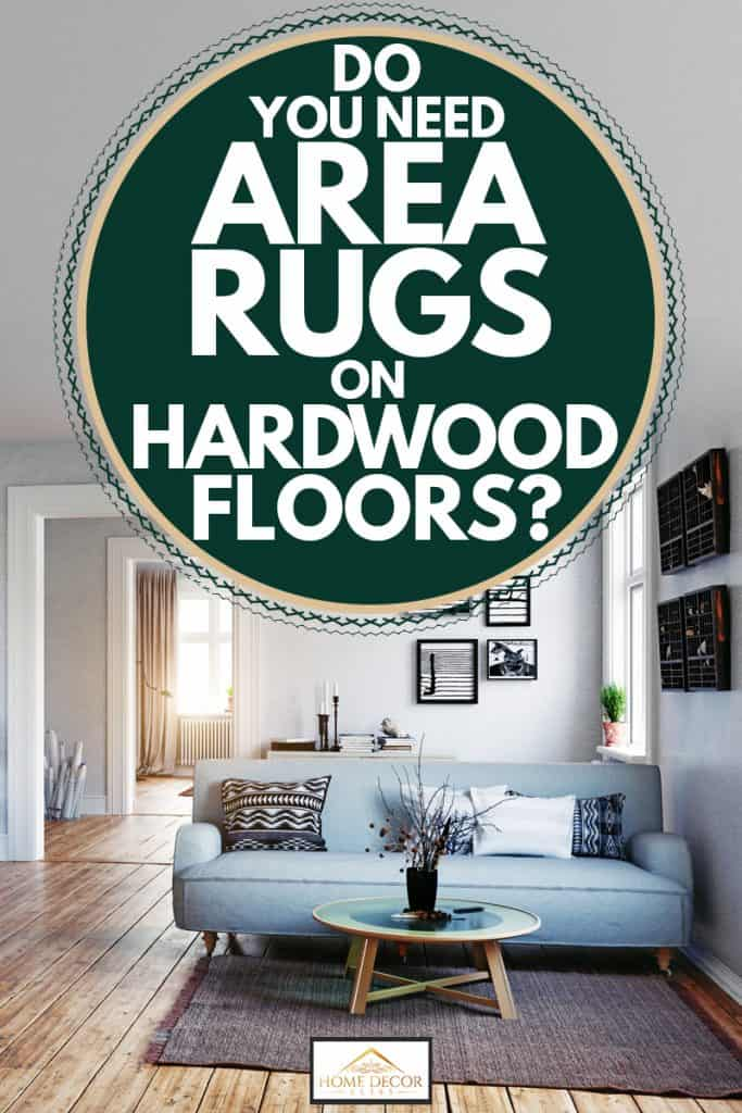 Modern living room with white light gray painted walls, hardwood flooring, and a light blue couch with an area rug underneath, Do You Need Area Rugs On Hardwood Floors?