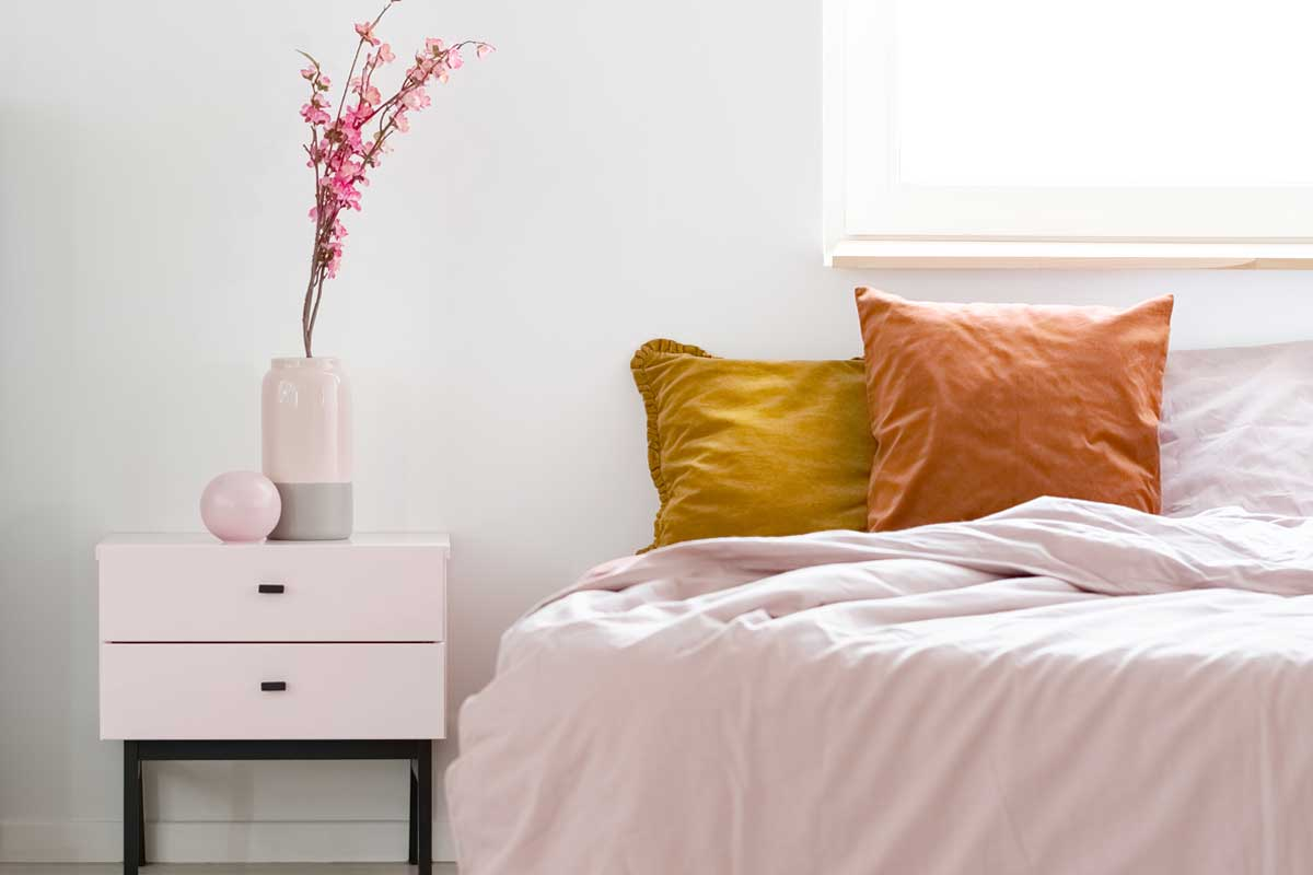 Feminine bedroom interior with pink sheets on a bed standing near wooden bedside table
