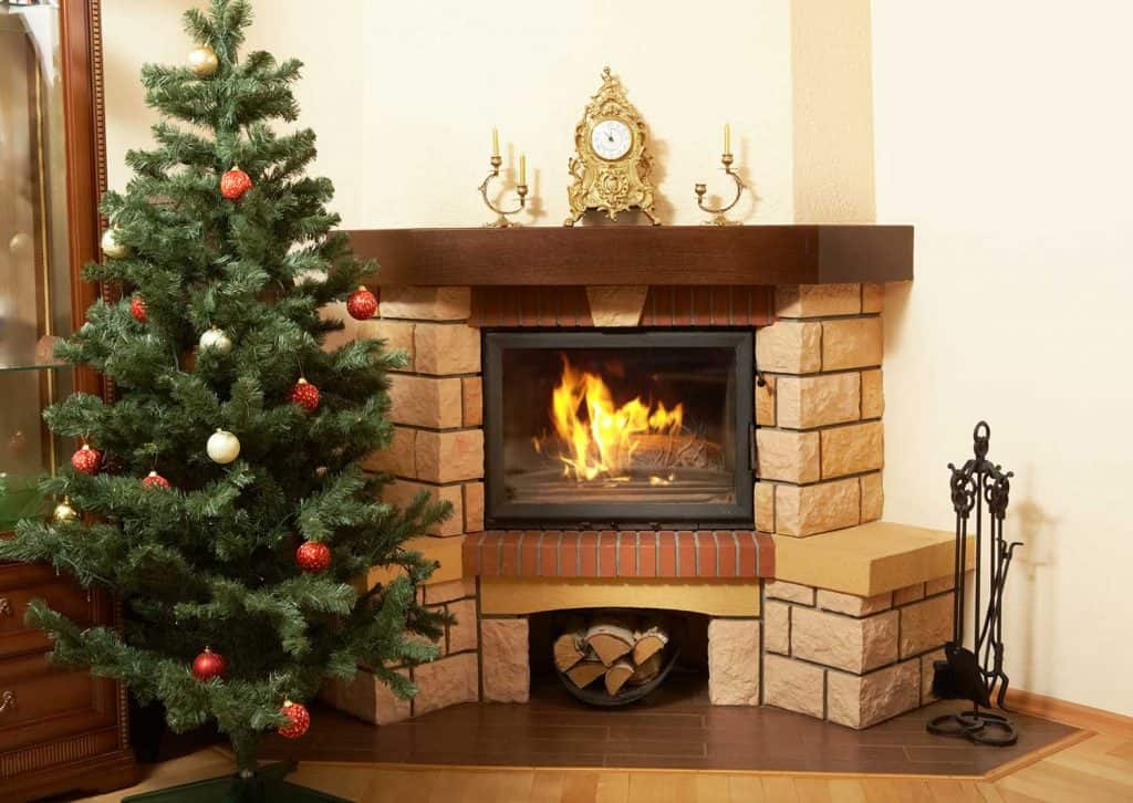 Fireplace with clock, candles and Christmas tree