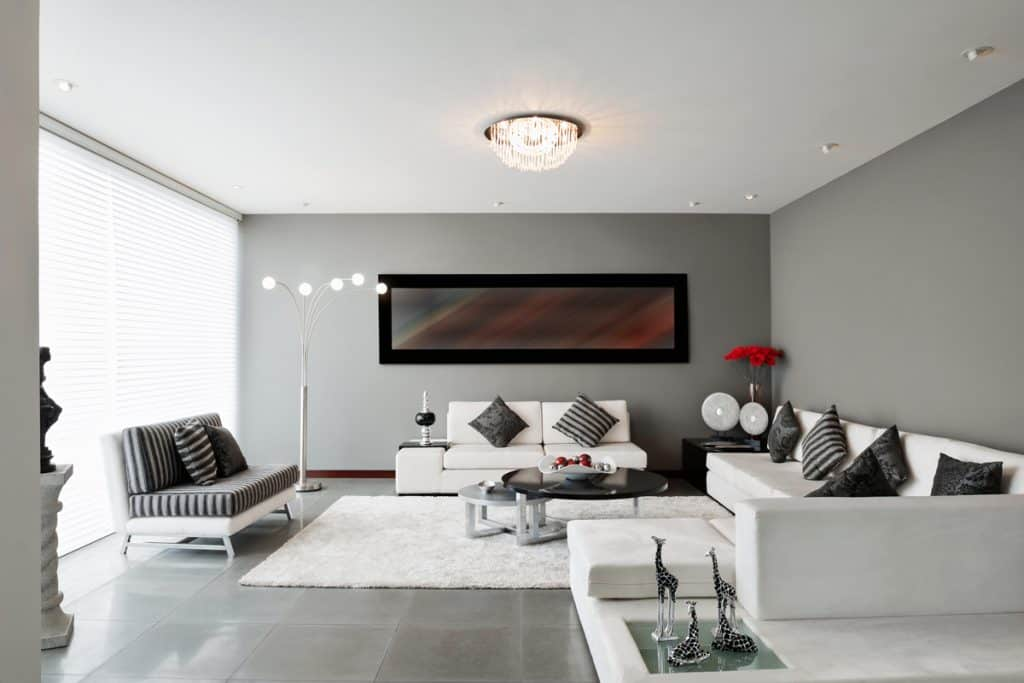 Gray and white themed living room with gray flooring and a black throw pillow blended with white couches