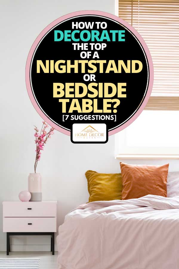 Bedroom interior with pink sheets on a bed standing near wooden bedside table, How To Decorate The Top Of A Nightstand Or Bedside Table? [7 Suggestions]