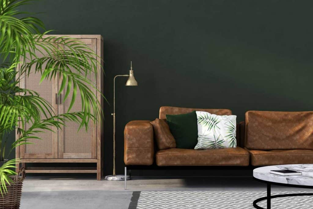 Interior of living room with brown leather sofa against a green wall