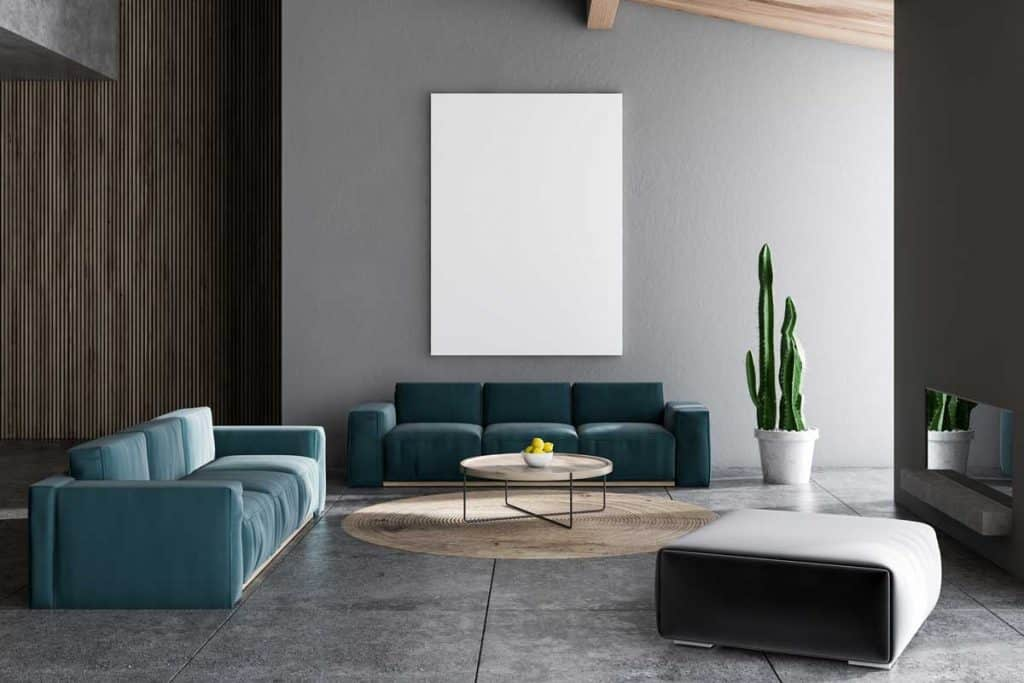 Interior of living room with gray and wooden walls, tiled floor, two blue sofas near round coffee table and fireplace. What Is the Best Size for Floor Tile?