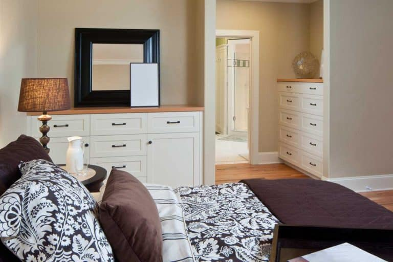 Master bedroom with dresser, lamp and mirror, What Do You Put Above A Dresser In A Bedroom? [6 Suggestions]