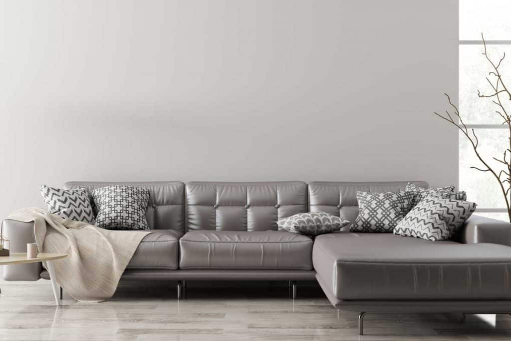 Modern interior of living room with brown leather corner sofa, coffee table,floor lamp