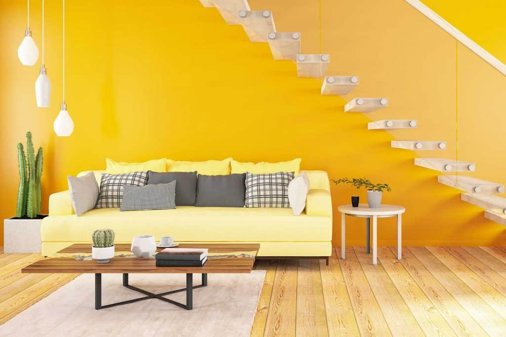Modern interior living room with mustard wall, stairs and furniture
