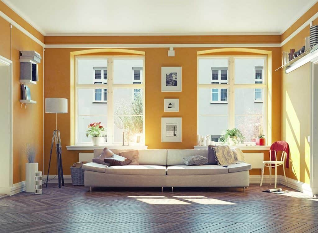 Modern living room interior with parquet floor, yellow walls and glass windows
