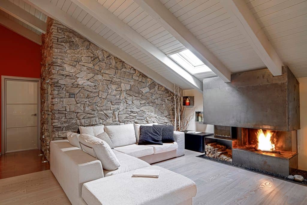 Modern living room with a stone decorated wall with protruding trusses and a white sectional chair