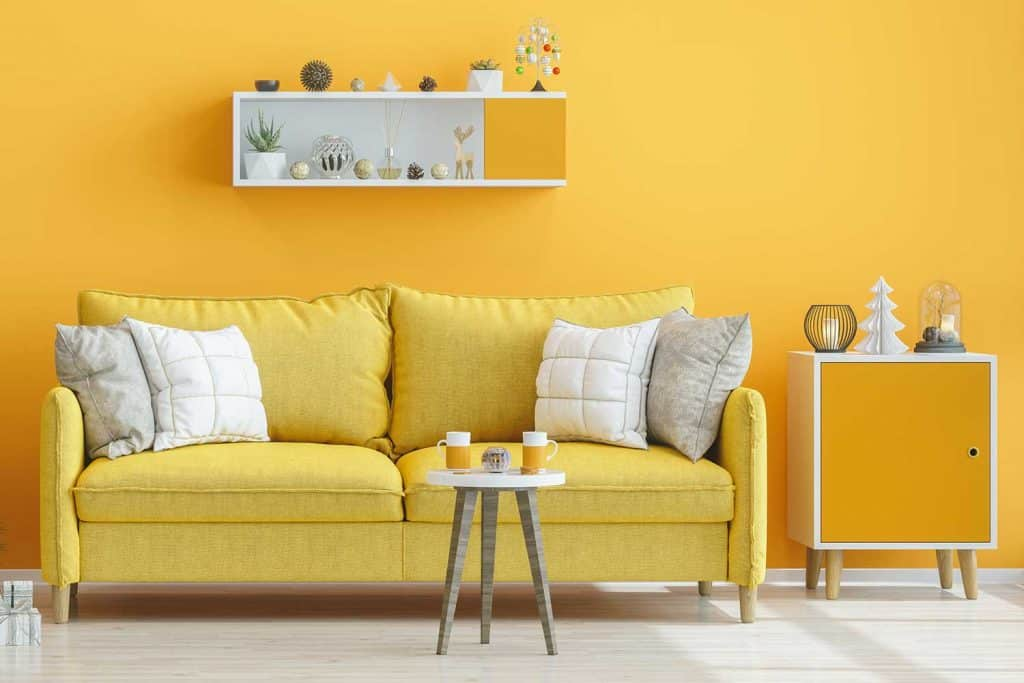 Modern living room with yellow couch and mustard yellow wall