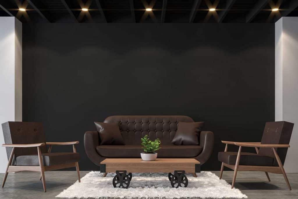 Modern loft living room with black and white.There are polished concrete floor,black wall and black wood ceiling furnished with brown leather furniture