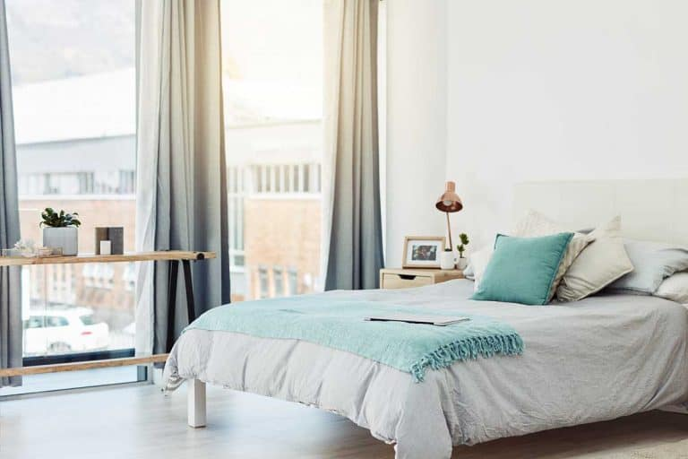 Neatly arranged bedroom at home with large glass window, Where To Put A Bed In A Room With Windows? [5 Practical Rules To Follow]