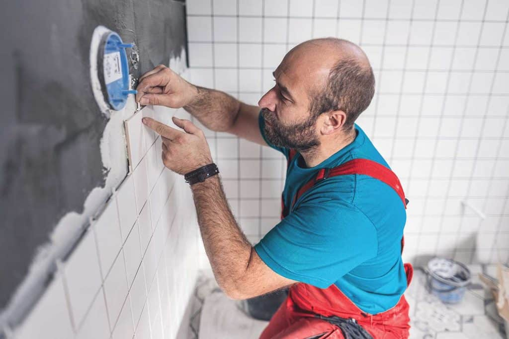 Professional tile worker putting spacers while installing tiles on the bathroom wall