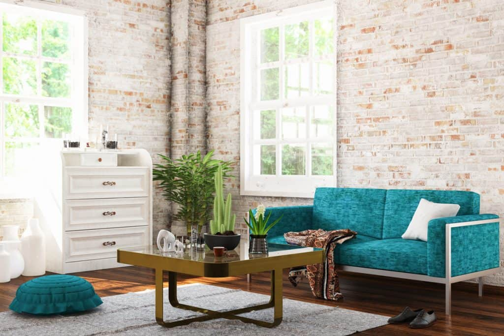 Stone decorated wall with a bluish color patterned chair with a glass top coffee table in front