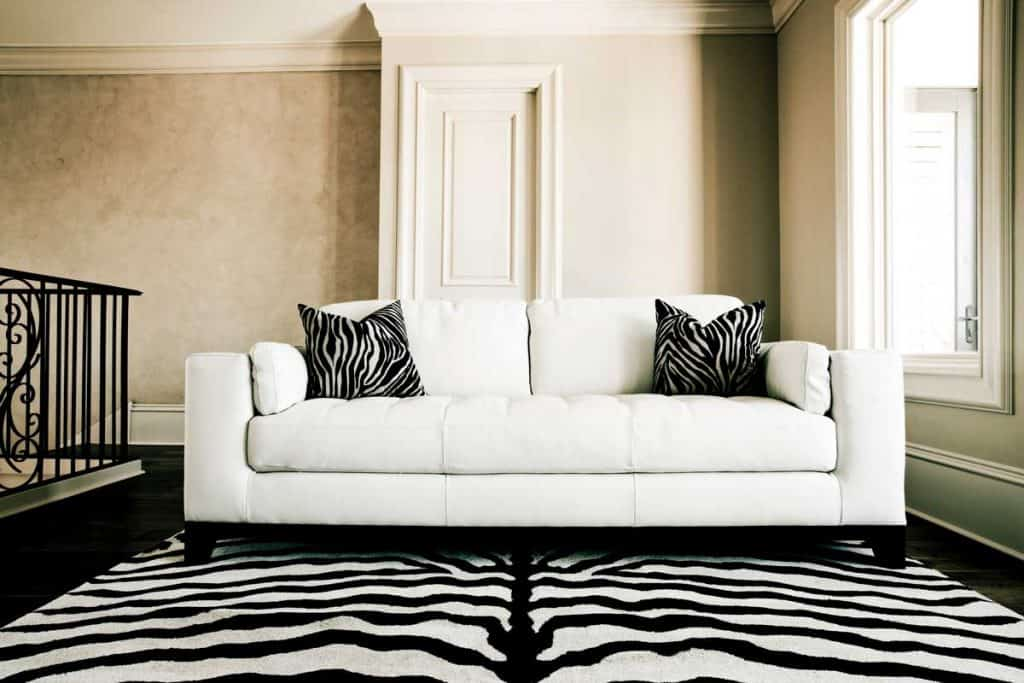 White leather couch with zebra-printed throw pillow case
