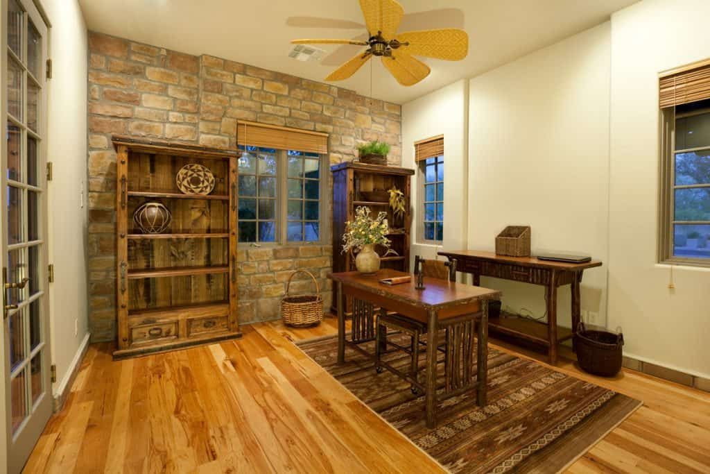 White walls and a stone decorated wall on the center blended with a wooden paneled flooring