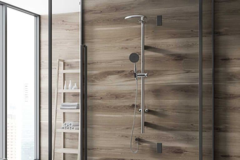 Wooden wall bathroom corner with a concrete floor, Are Shower Panels Better Than Tiles?
