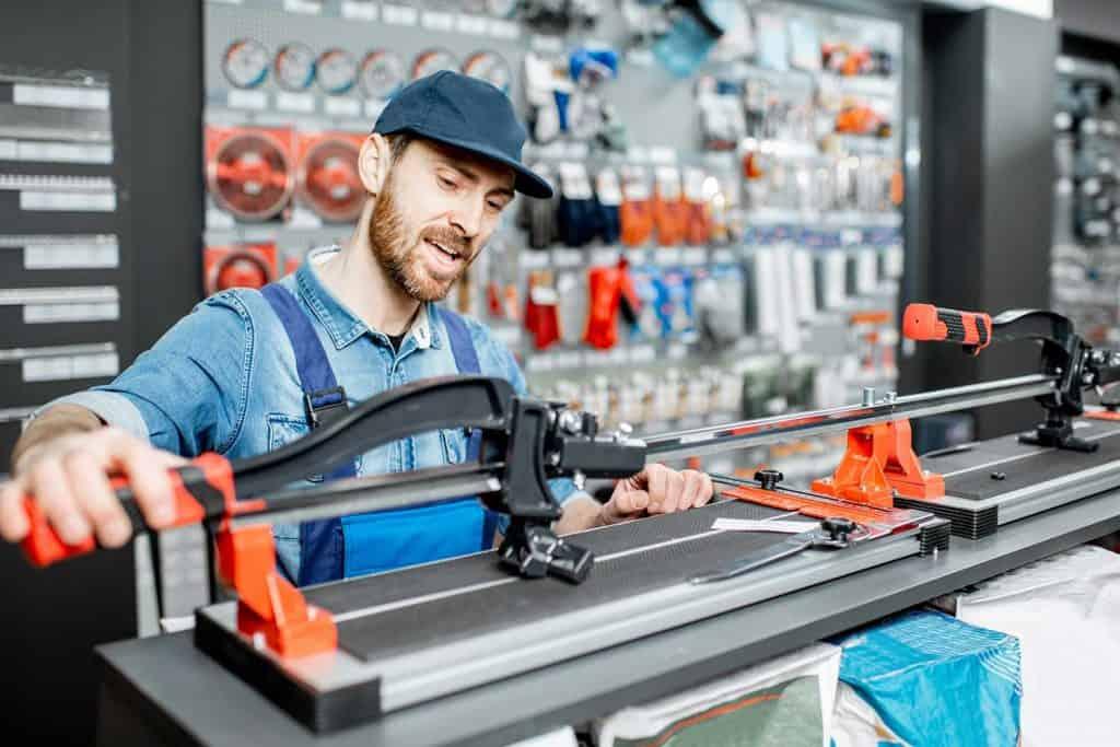 Workman in uniform choosing professional tile cutter in the building shop