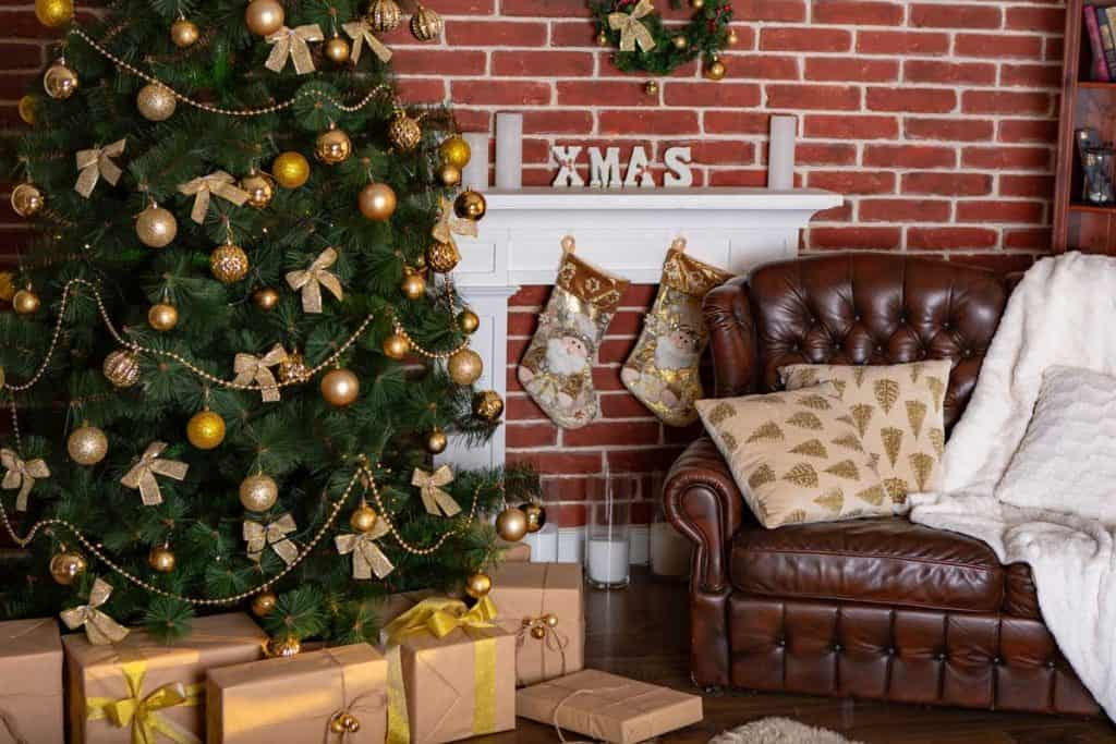 beautiful location with a decorative fireplace and gifts under the Christmas tree and a leather chair with pillows in the room