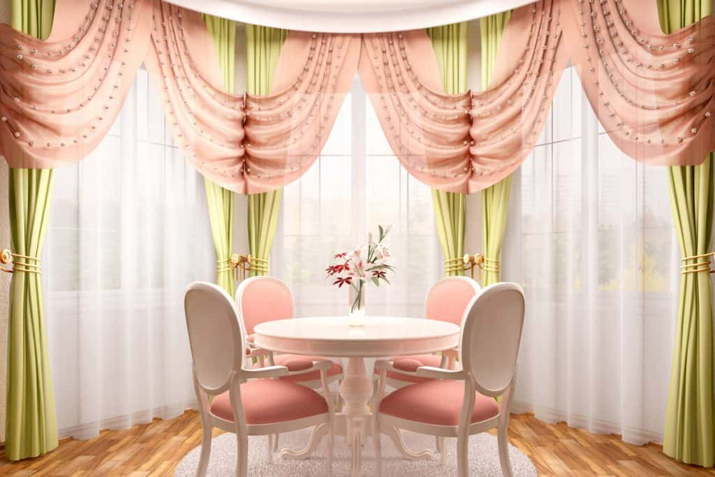 A bay window incorporated with pink and light green colored curtains with a mixture of pink and white dining chairs